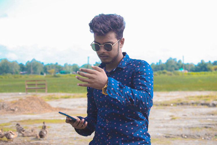 Young man using mobile phone on field