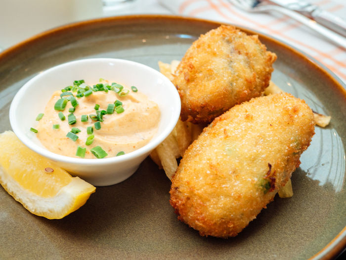 Close-Up Of Croquette With Cheese Dip In Plate