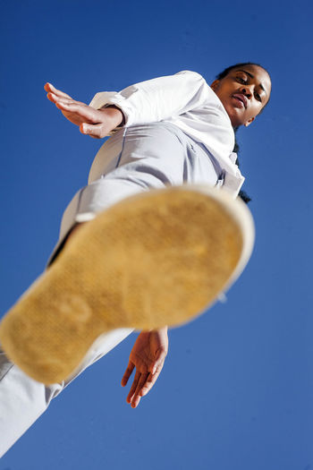 Low angle view of man hand against clear blue sky