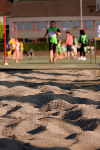 Close-up of sand with people playing in background