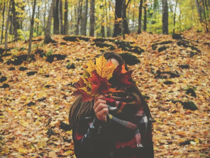 Woman holding autumn leaves while standing on field