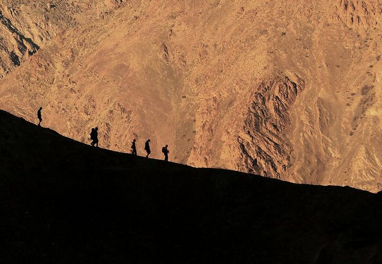 Silhouette people hiking on mountain