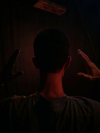 Rear View Of Man Gesturing In Darkroom