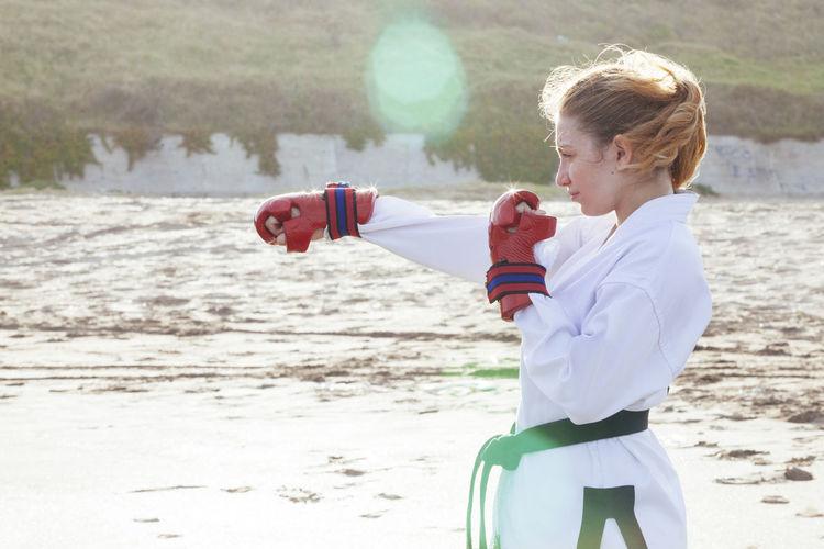 Cute girl practicing karate on beach