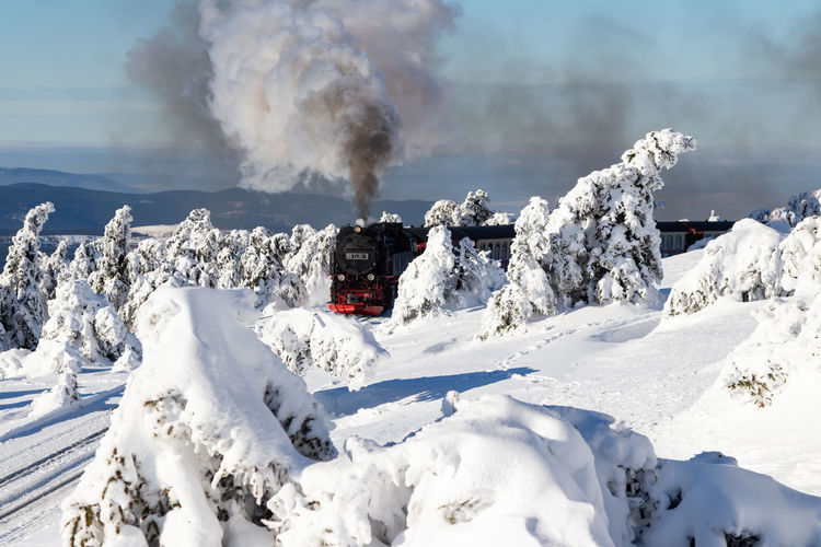 Winter landscape with old steam locomotive (Brockenbahn) on the Brocken, Harz National Park. Germany Steam Locomotive Brockenbahn White Snow Winter Beauty In Nature Panoramic View Snowcapped Mountain Mountain Peak Smoke - Physical Structure Blue Sky Sunlight Cold Temperature Tourists Holiday Destination National Park Bizarre Shapes Snow Covered Trees Old Historical Train Technology Romantic Nature Landscape