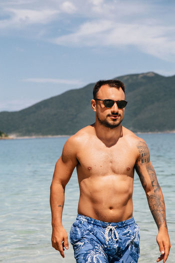 Water Shirtless Young Men Sea Young Adult Lifestyles One Person Sunglasses Fashion Real People Front View Leisure Activity Standing Beauty In Nature Three Quarter Length Beach Nature Sky Land Outdoors