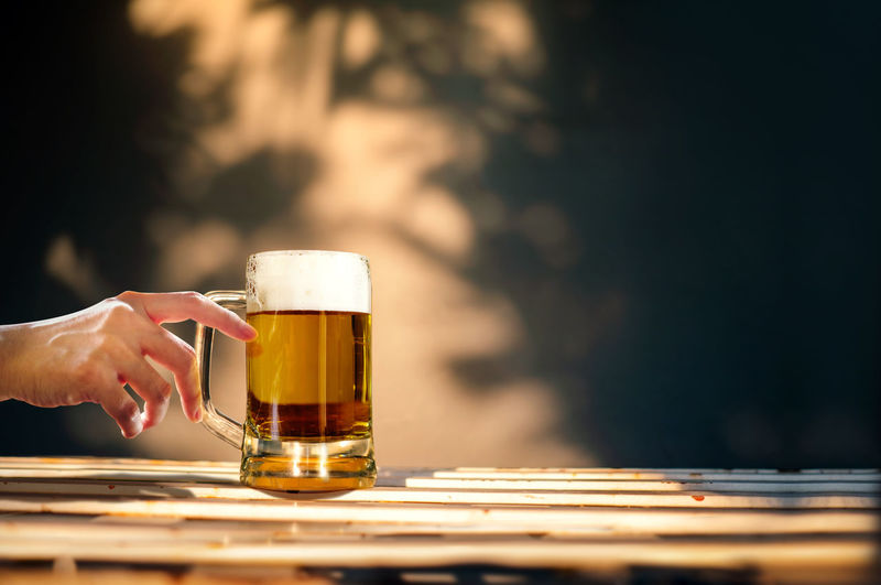 a Glass of Beer on Table in Summer Sunny Day. People Drinking Brew. Shadow of Tree as background Beer Drink Summer Sunny Sunlight Relaxing Relaxation Woman Female Girl People Brew Foam Lager Hand Holding Touch Nature Lifestyle Celebration Time Sunset Concept Drinking Happy Leisure Outdoor Day Photo Copy Space Beverage Refreshment Craft Pint Oktoberfest Restaurant Cafe House Home Table Full Drunk Cold Body Part Selective Focus Beer Glass Finger