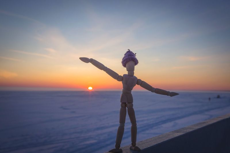 Close-Up Of Wooden Figurine On Retaining Wall By Frozen Lake During Sunset