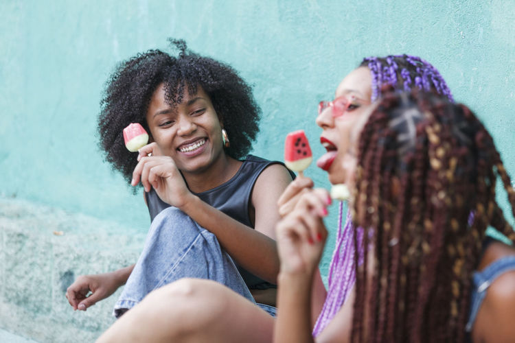 Female friends eating flavored ice while sitting outdoors