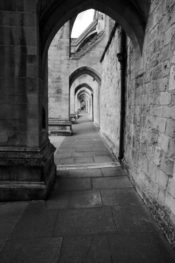 Winchester Cathedral Arcade Black & White Alley Arcade Arch Arched Architectural Column Architecture Building Building Exterior Built Structure Colonnade Corridor Day Diminishing Perspective Direction Empty Footpath History Long No People Outdoors The Past The Way Forward Wall Wall - Building Feature