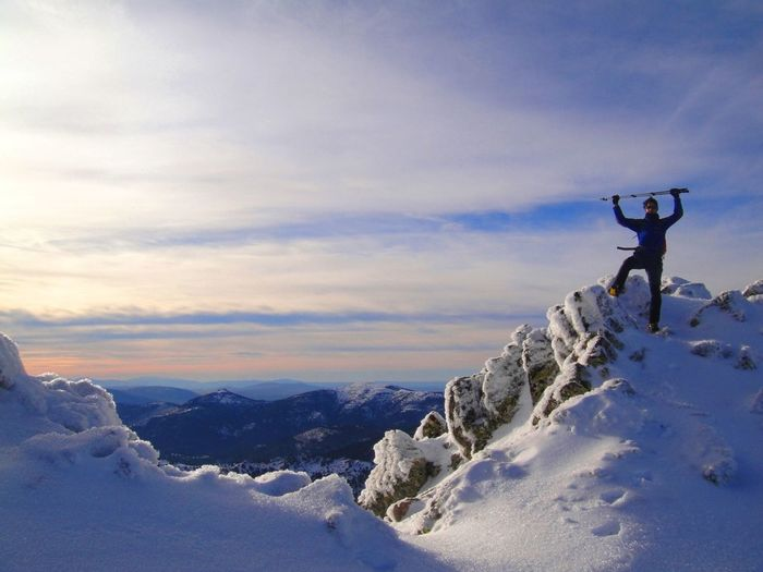 Man holding ski poles while standing on snowcapped mountain at guadarrama