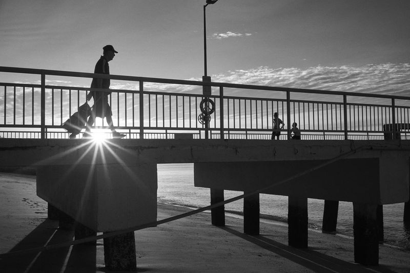 Silhouette of person crossing Bedok Jetty during sunrise B&w Bedok Jetty Black And White Bridge Men Morning Light Railing Railings Sea Shadow Silhouette Singapore Sky Streetphotography Sunrise