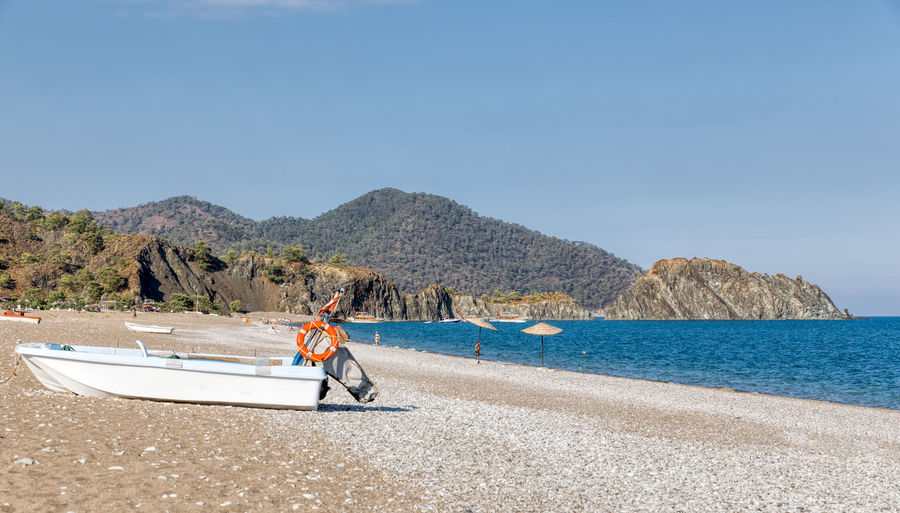 Natural beach of Turkish Riviera with boats in Cirali, Turkey. Anatolia Antalya Turkey Türkiye ASIA çıralı Incidental People Boat Motorboat Bay Of Water Beach Beachphotography Beach Photography Beach Life Life Is A Beach Natural Beach Cliff Coast Coastline Rocky Coastline Headland Rock Formation Landscape Landscape_Collection Majestic Mediterranean  Mediterranean Sea Moored Mountain Panorama Pebble Pebble Beach Relaxing Scenery Tourism Tourist Seascape Shore Stationary Sand Tranquility Empty Absence Abandoned Turkish Riviera Vacations Travel Destinations Water Sky Day Sea Nature Transportation Scenics - Nature One Person Beauty In Nature Men Clear Sky Copy Space Real People Mode Of Transportation Nautical Vessel Sunlight Full Length Outdoors