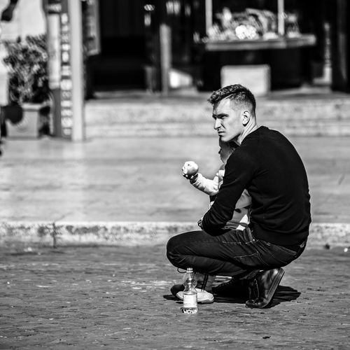 """""""Dad's Protection"""" Apple Italy Streetphotography Girl Daughter Skill  Looking Away Holding Sitting Crouching Young Adult Focus On Foreground Lifestyles Men Young Men Leisure Activity Full Length Real People One Person EyeEm Best Shots EyeEm Selects Dad The Art Of Street Photography My Best Photo"""