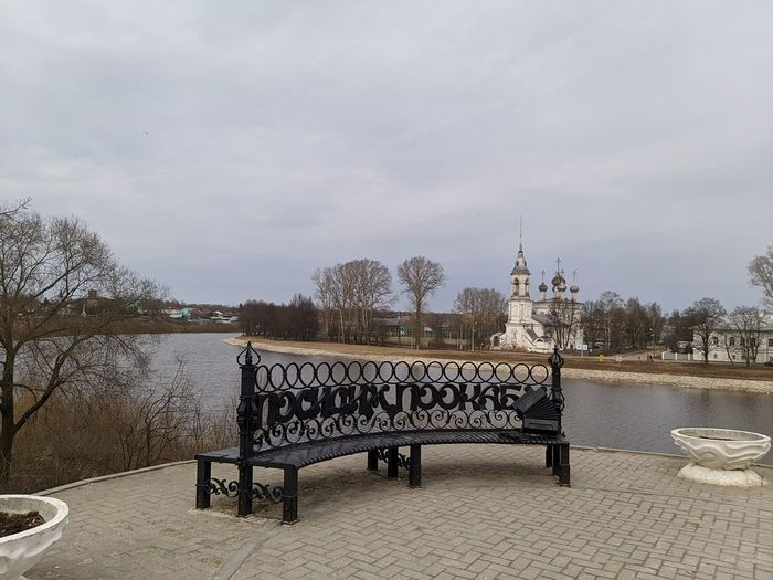 Empty benches in river against buildings