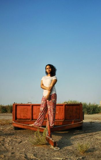 Portrait of young woman on a wagon standing next to the clear blue sky.