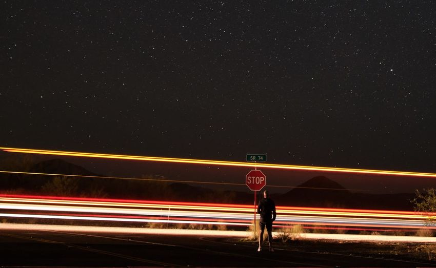 Man standing by light trails on road against sky at night