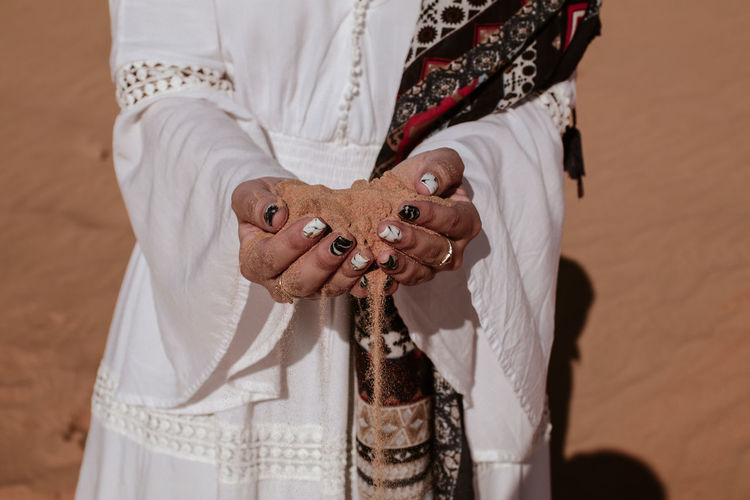Close-up of female hand releasing dropping sand. Sand flowing through the hands in desert Midsection One Person Holding Focus On Foreground Front View Human Hand Hand Real People Traditional Clothing Adult Clothing Religion Women Human Body Part Lifestyles Jewelry Day Men Indoors  Sand Climate Change Global Warming Nature Summer Holiday Woman Closeup Beach Pouring Fingers Fall Brunette Vacations Females Sunny Hot Portrait Atmosphere Ecology Pours Fingernail Close-up Stream Desert Flowing Sunbathing Landscape Bankrupt Travel Nail
