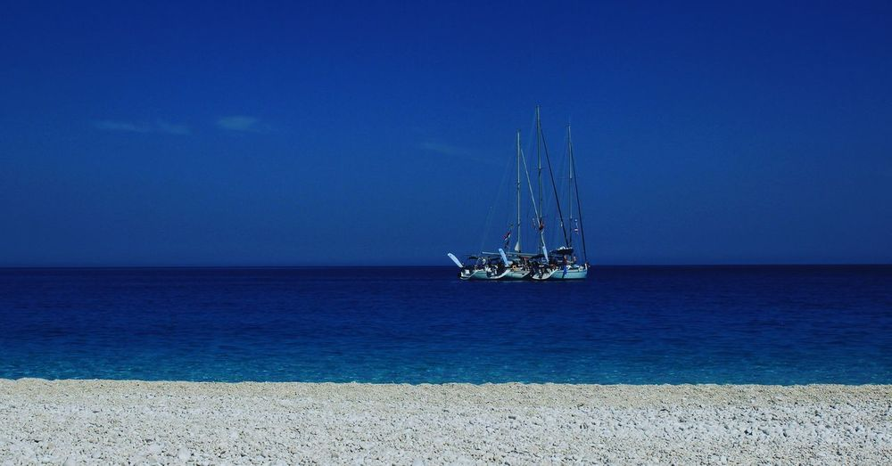 Sailboat In Sea Against Blue Sky