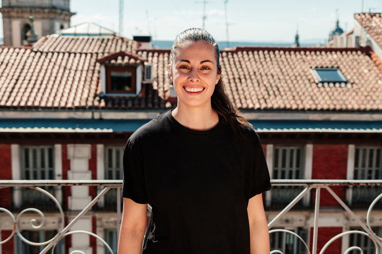 Portrait of smiling young woman standing against building