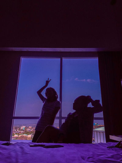 Silhouette couple against window in bedroom