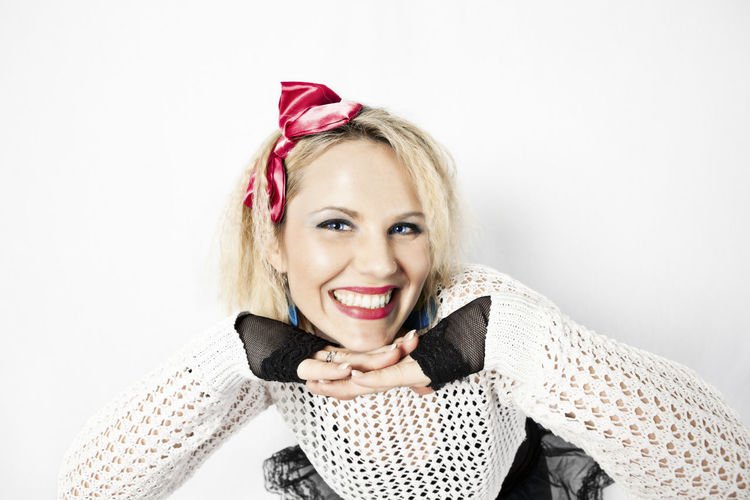 Beautiful blond woman dressed in 1980s retro fashion smiling, looking at camera with chin resting on hands 1980s 1980s Style 80s Beautiful Dressed Up Fashion Portrait Of A Woman Retro Woman Blooming Caucasian Costume Cute Female Hands On Chin Happiness Looking At Camera Mid Adult Woman One Person Portrait Posing Smiling Style Toothy Smile White Background