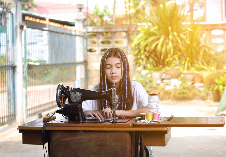 Girl with long hair learning sewing while sitting outdoors