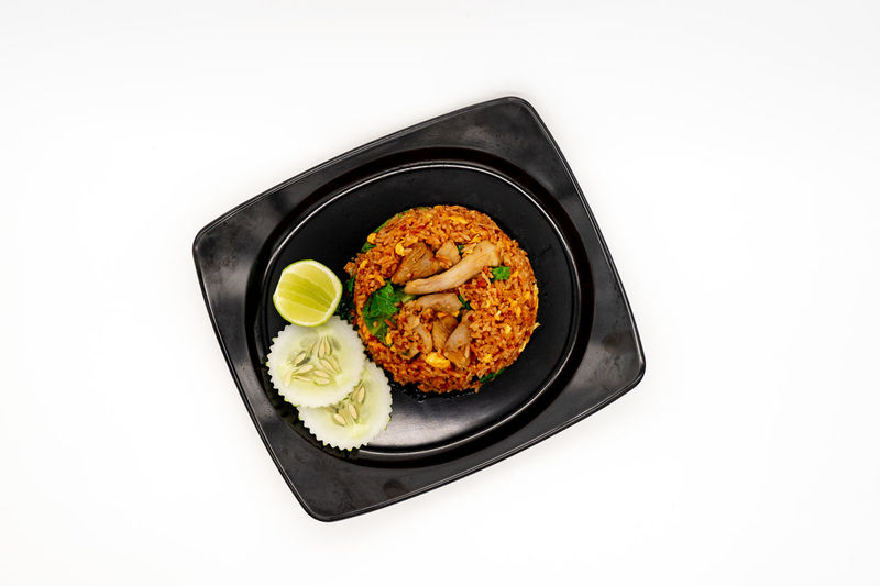 High angle view of food in plate against white background