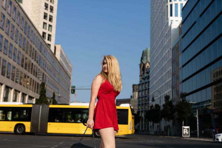 Woman looking away while standing on road against bus and buildings in city
