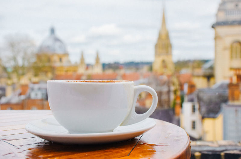 Close-up of cup on table against buildings in city