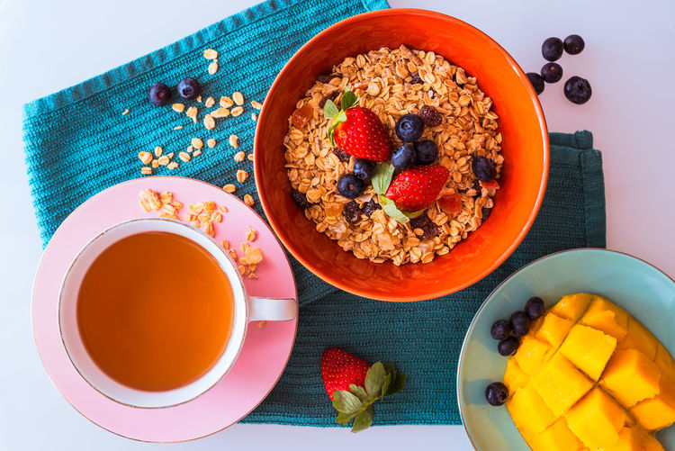 Breakfast with tea, oats and fruits Mango Berry Fruit Blueberry Bowl Breakfast Breakfast Cereal Crockery Cup Drink Eating Utensil Food Food And Drink Freshness Fruit Healthy Eating Meal No People Oats - Food Refreshment Still Life Strawberries Table Tea Cup Wellbeing