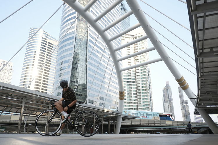 Man riding bicycle on modern building in city