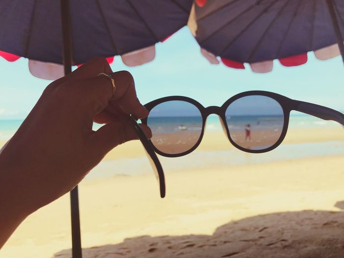Cropped image of hand holding sunglasses on beach