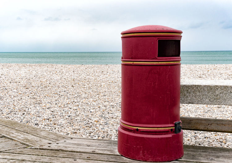 Red container on beach against sky