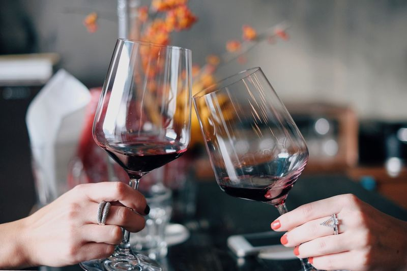 Cropped hands of women toasting red wine at restaurant