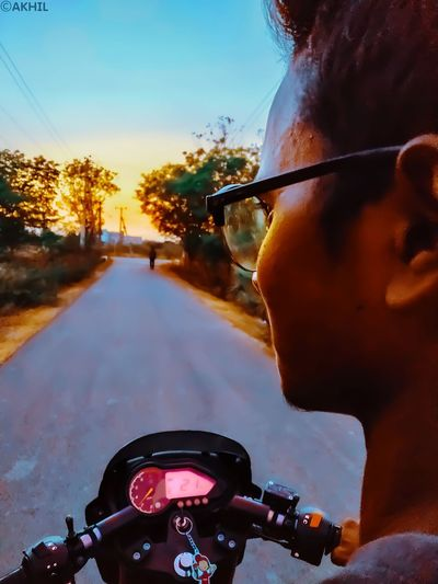 Close-up of man riding motorcycle on road in city