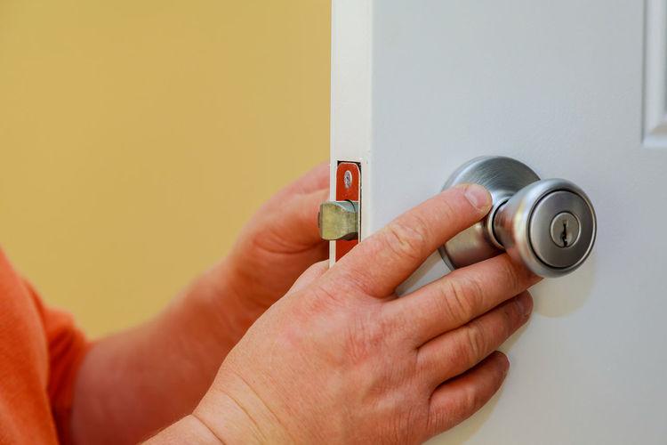 Cropped hands holding doorknob