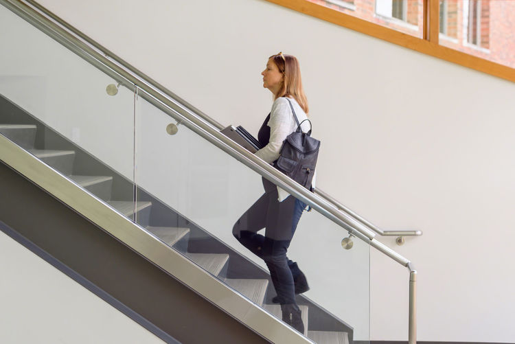 Low angle view of woman standing on staircase