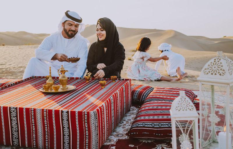 Happy family having tea on carpet at desert