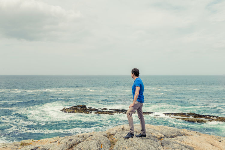 Full length of man standing on rock at sea shore against sky