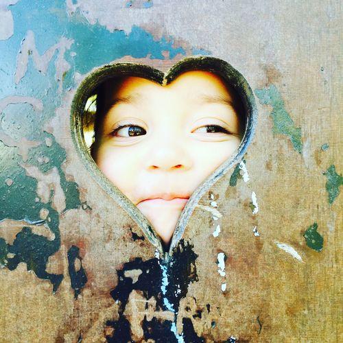 Smiling cute girl peeking through heart shape
