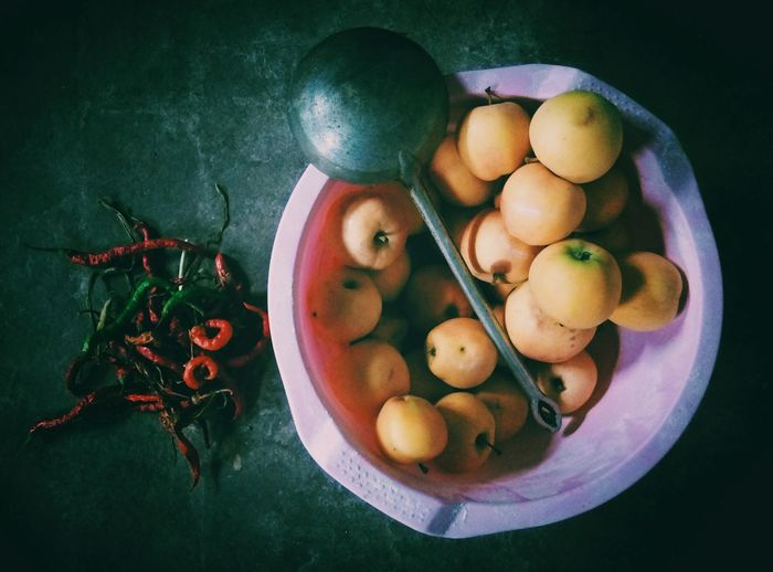 Directly above shot of apples and ladle in basket by chili pepper on table
