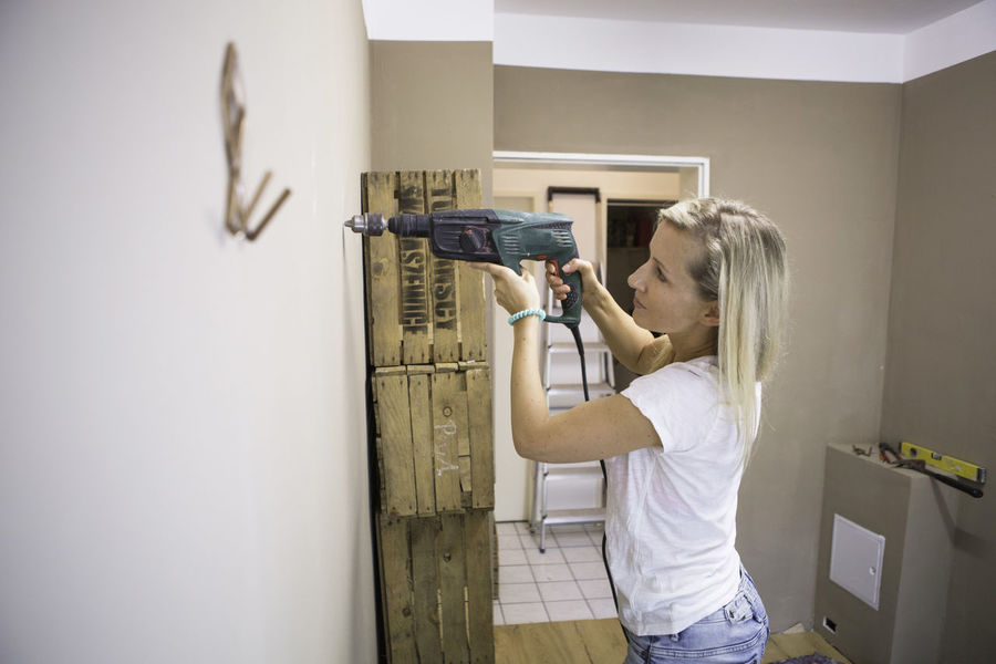 Young lady drilling into a changing room wall in a yoga studio Blond Hair Casual Clothing Changing Rooms DIY Diy Project Drilling Leisure Activity Lifestyles Renovations Skill  Skilled Work Yoga Studio Young Lady