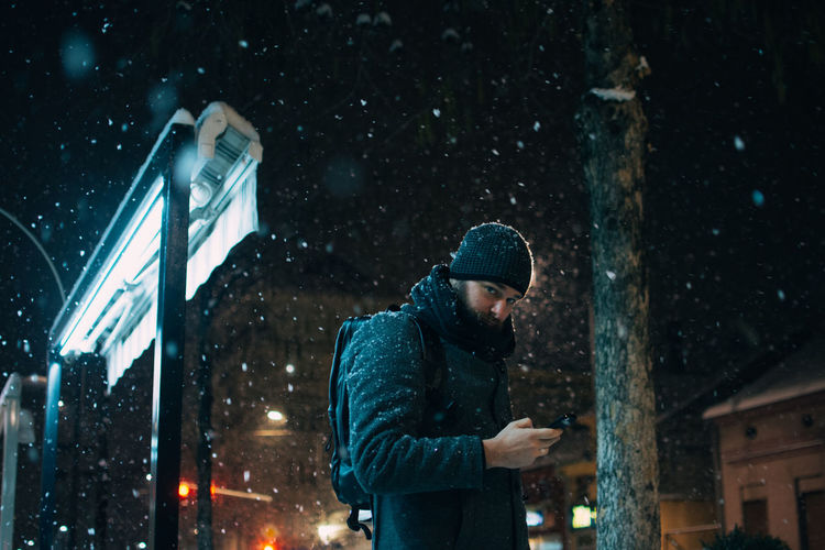Man using mobile phone while standing against building during snowfall at night