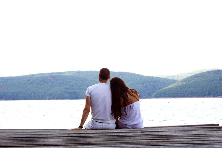 Young Couple Sitting On Pier While Looking At Lake Against Sky