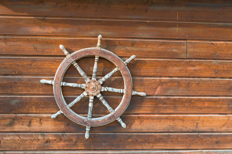 Close-up of bicycle wheel on wooden wall