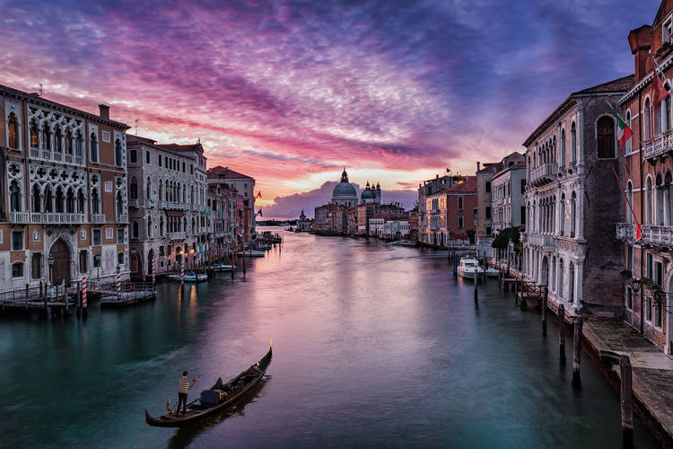 Sunrise over the Grand Canal in Venice, Italy, with a gondola passing by Basilica Cathedral Reflection Romantic Tourist Attraction  Travel Architecture Attraction Bridge Building Exterior Canal Clouds Dawn Gondola - Traditional Boat Intense Italy Nautical Vessel Sky Sunrise Tourism Transportation Travel Destinations Veneto Venice Water