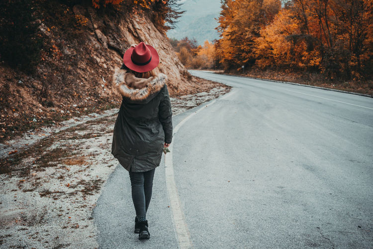 Woman with hat exploring the autumn mountain