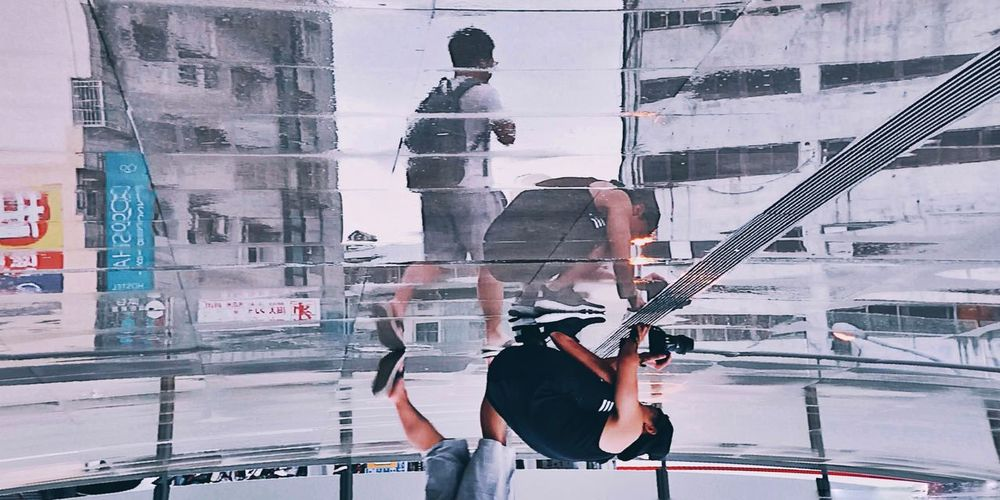 People working on glass building in city