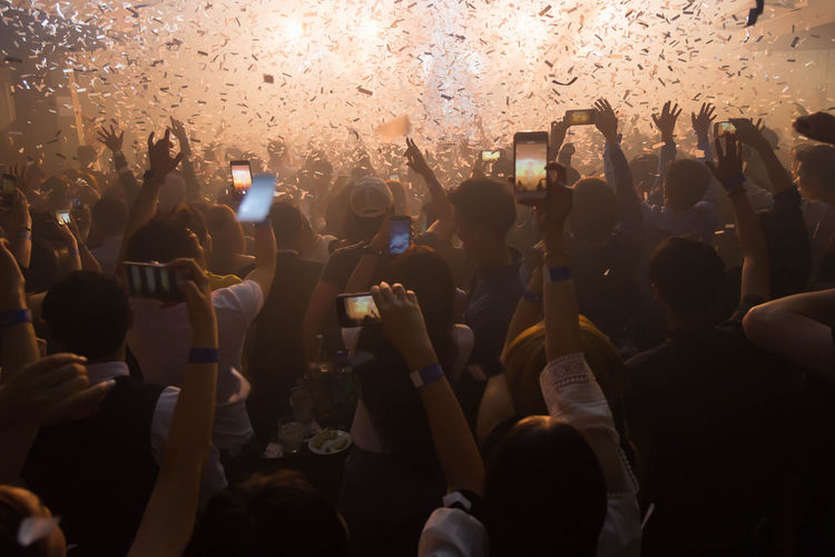 Group of people using mobile phones at music concert